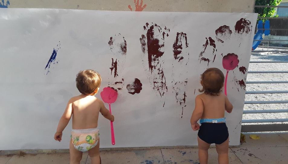 Dos infants pintant en una paret a la llar d'infants del Morell.