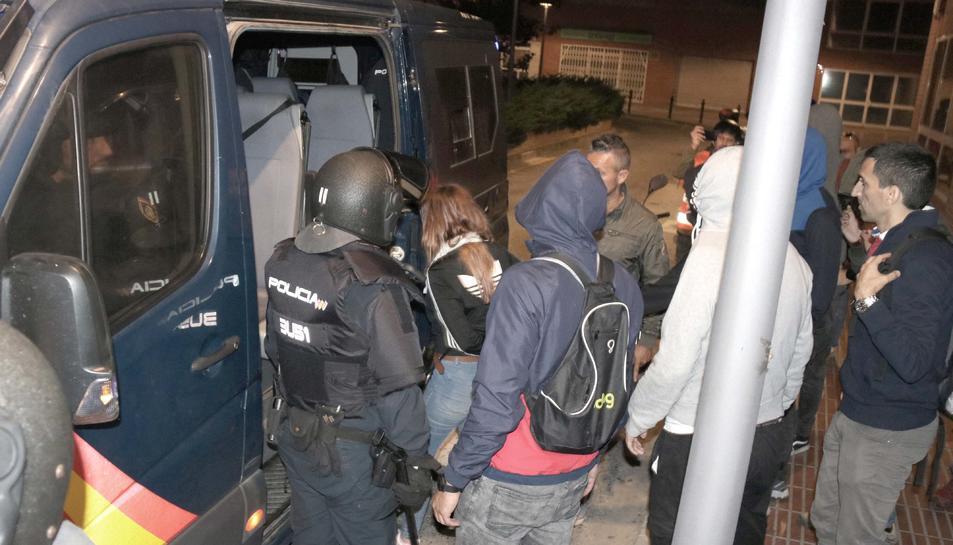 La noia detinguda pujant a la furgoneta de la Policia Nacional, envoltada d'agents, durant els aldarulls d'aquesta nit de dijous.