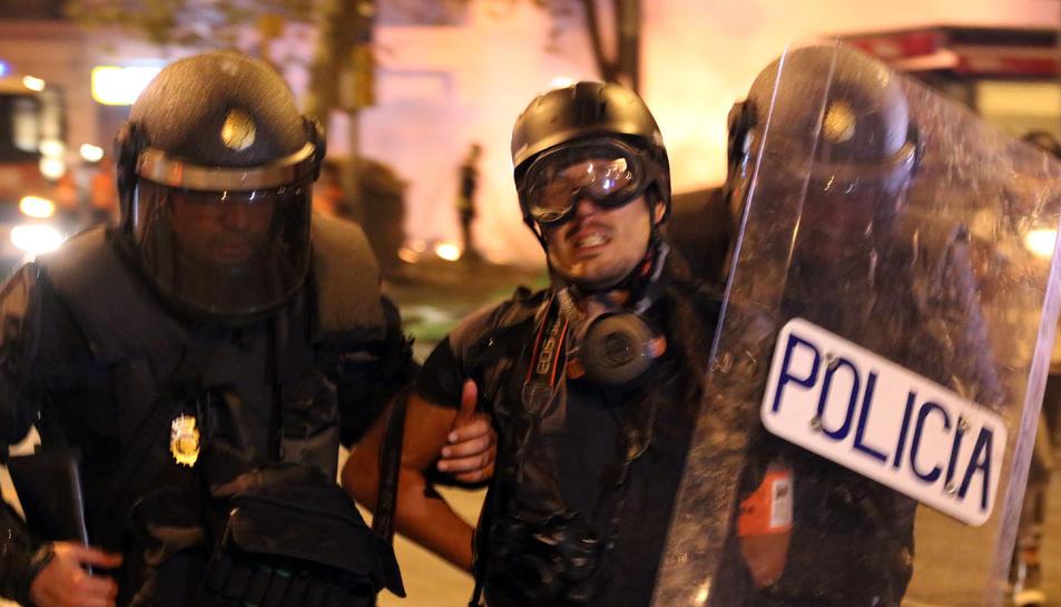 La Policia Nacional s'endú detingut i emmanillat per l'esquena el fotoperiodista d'El País Albert Garcia a la plaça Urquinaona de Barcelona.