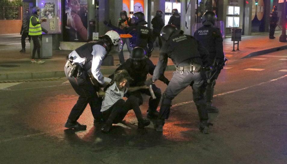 Pla general dels Mossos d'Esquadra detenint un manifestant durant la quarta nit d'aldarulls a Tarragona.