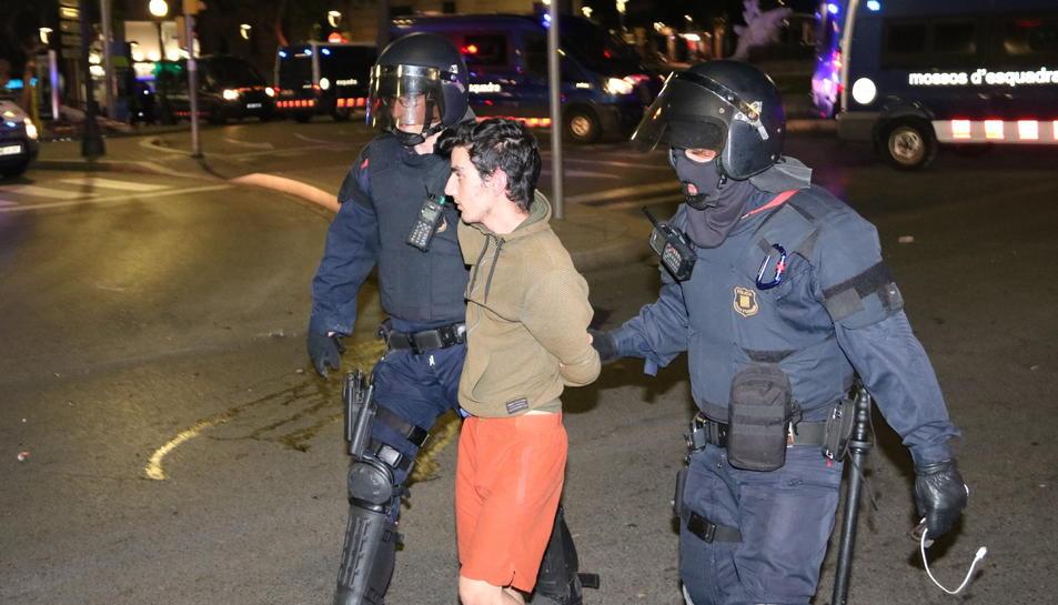 Pla mitjà de dos agents i un manifestant detingut a la font del Centenari de Tarragona durant els aldarulls a la ciutat.
