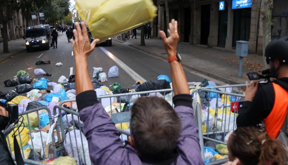 Un home llança una bossa d'escombraries a l'entorn de la delegació del govern espanyol a Barcelona.
