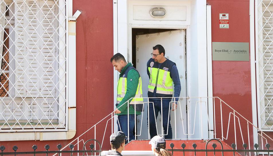 Dos agents de paisà amb armilles grogues de la Policia Nacional surten del despatx de l'advocat Gonzalo Boye.