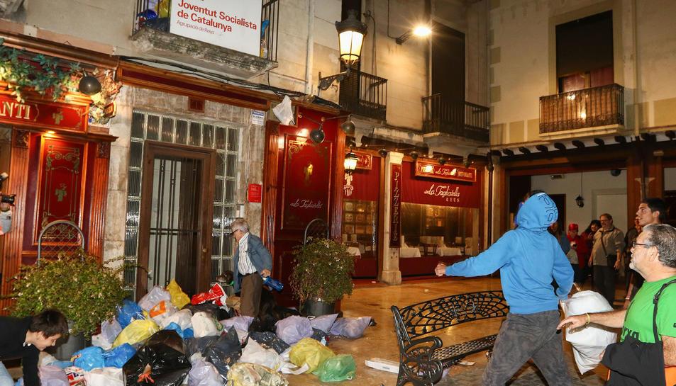 Un veí intentant accedir al portal mentre es continuaven llençant bosses a la seu del PSC.