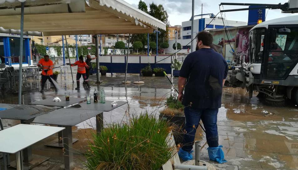 Albert Mateu, propietari de L'Arrosseria –d'esquena– durant les tasques de neteja de la terrassa de l'establiment del Serrallo.