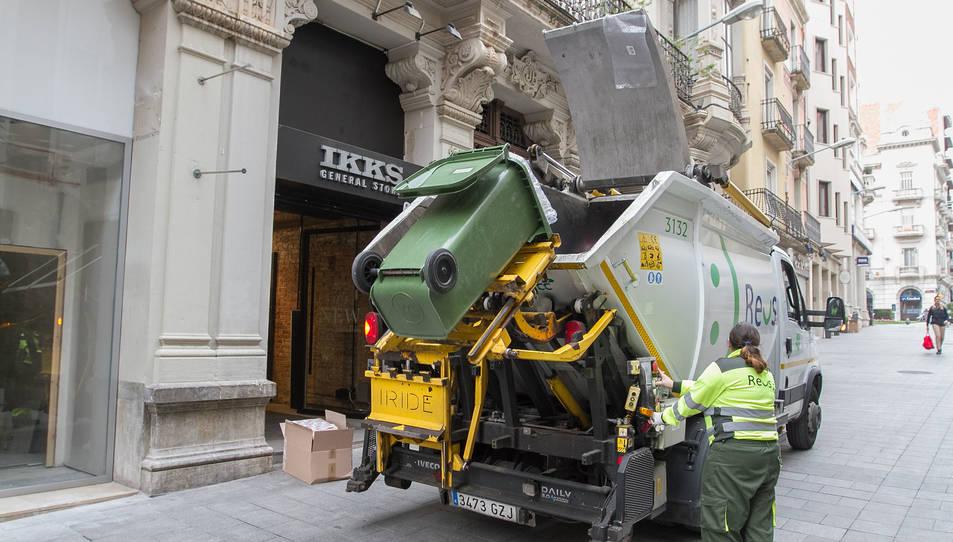 Imatge d'arxiu d'un camió i una treballadora realitzant les tasques de neteja al centre de Reus.