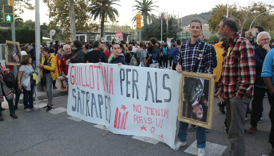 Uns manifestants aguanten una pancarta en contra de la visita del rei Felip VI a Barcelona