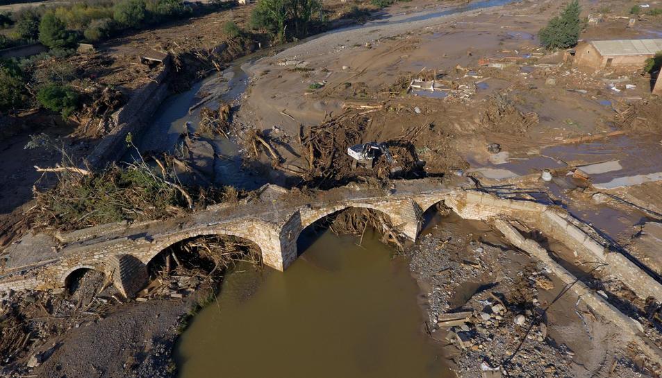 Imatge aèria picada del Pont Vell de Montblanc, amb la llera del riu plena d'arbres i de fang.