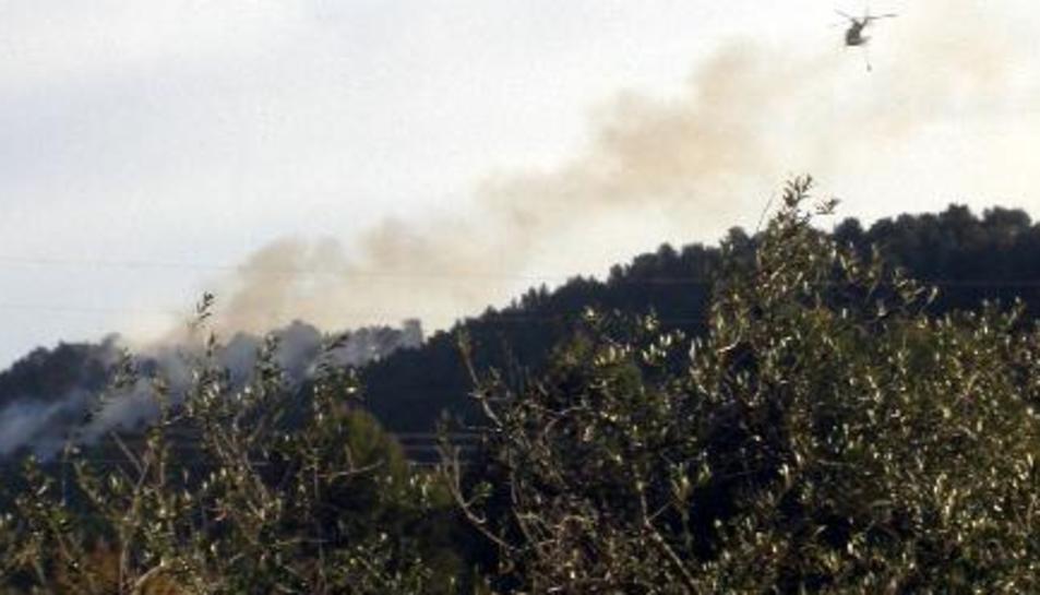 Un helicòpter bombarder sobrevolant l'incendi declarat en una parcel·la de les Borges del Camp.
