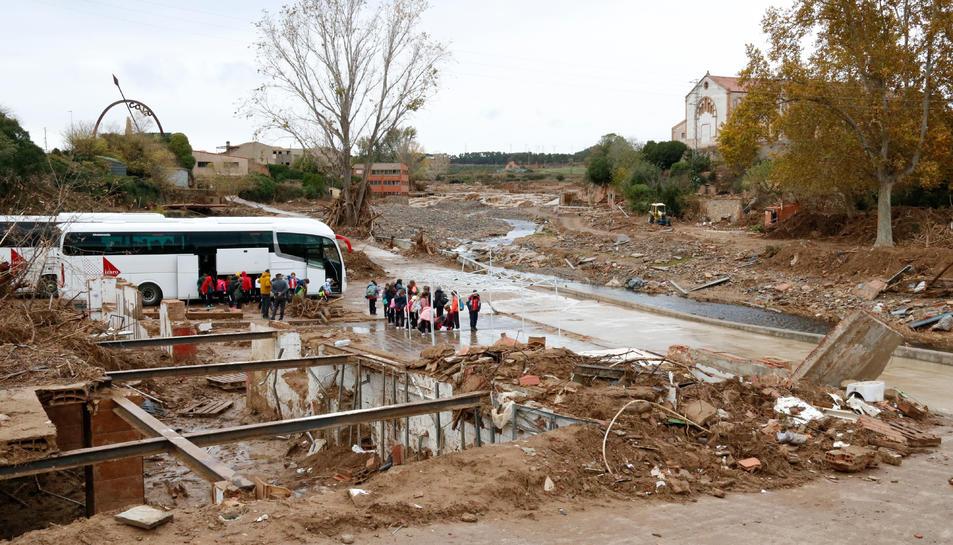 Pla general del riu Francolí al seu pas per l'Espluga de Francolí, de les destrosses a la llera i, al fons, un grup d'escolars de Barcelona baixant d'un autobús, de visita al poble. Imatge del 14 de novembre del 2019