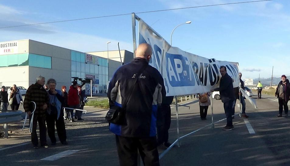 Pla general dels participants al 239è tall de l'N-340 a Amposta situant la pancarta que els ha acompanyat aquests quatre anys de lluita.