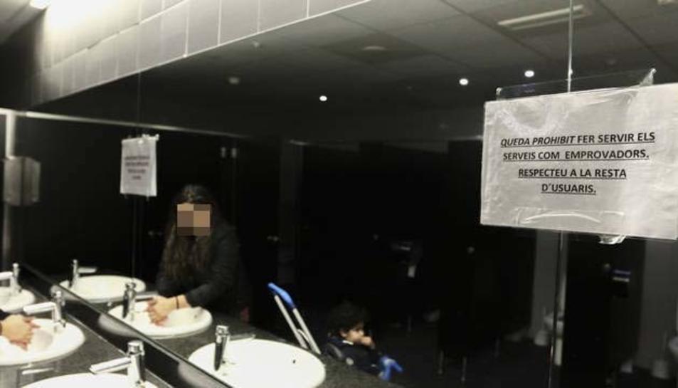 En primer terme, cartell informatiu en el mirall dels lavabos públics de dones del Mercat Central.