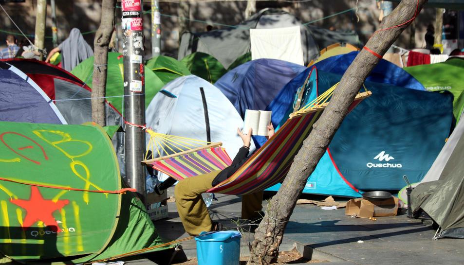 Una persona descansa llegint a l'acampada de Plaça Universitat.