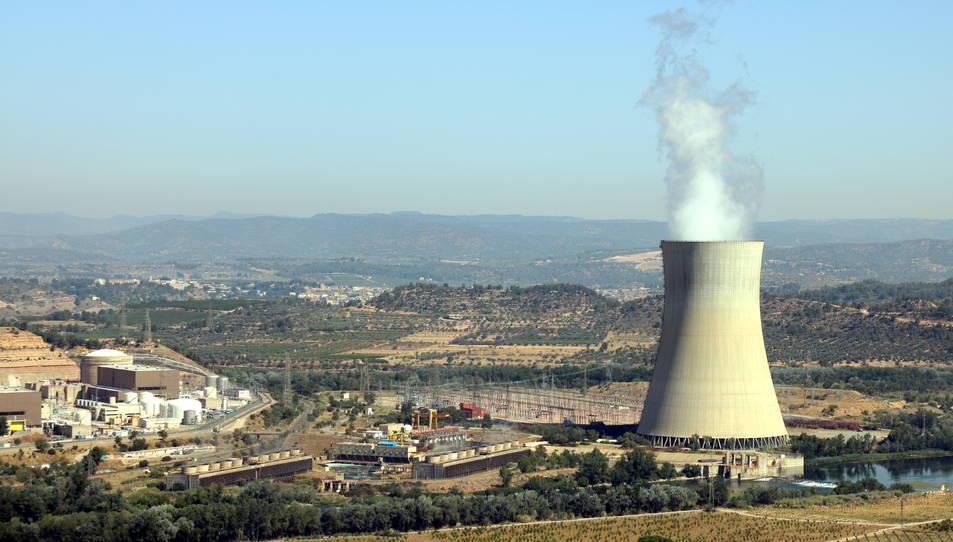 Imatge de la central nuclear d'Ascó, a la Ribera d'Ebre, amb la xemeneia fumejant a la dreta i els dos reactors a l'esquerra.