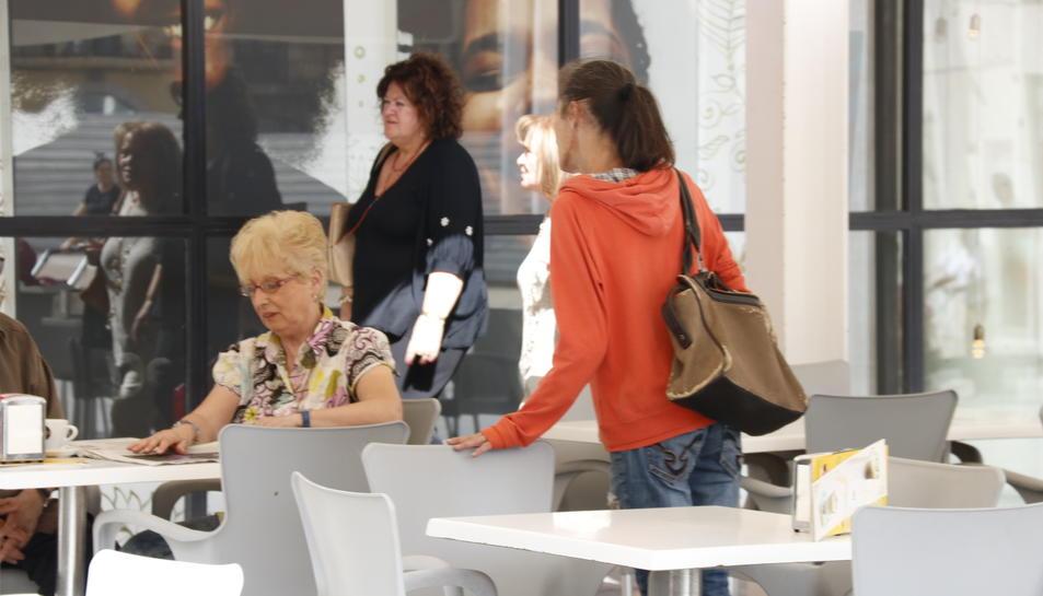 Una dona demanant almoina a clients d'una cafeteria, en una terrassa al centre de Reus.