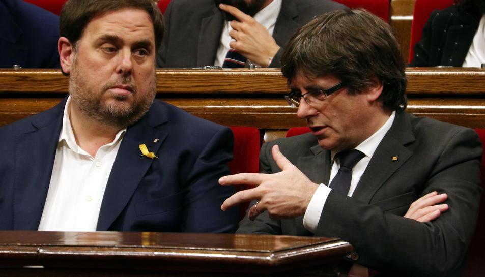 El president de la Generalitat, Carles Puigdemont, parla amb el vicepresident, Oriol Junqueras, al Parlament.