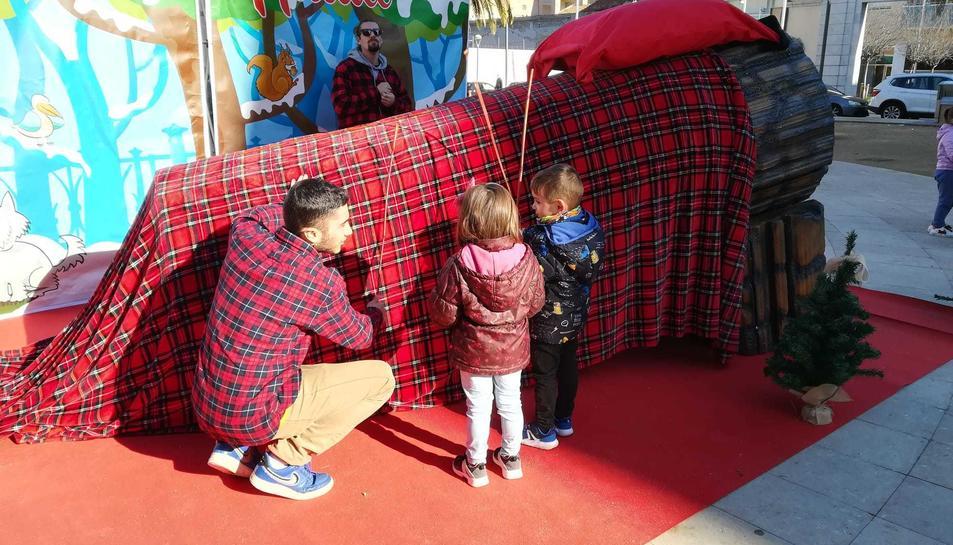 Dos nens fan cagar un tió de grans dimensions a la plaça dels Infants.