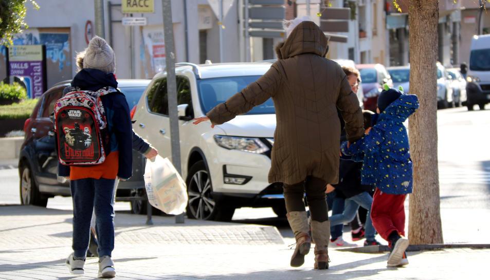 Imatge d'una dona i de dos menors caminant a Valls enmig d'un fort vent.