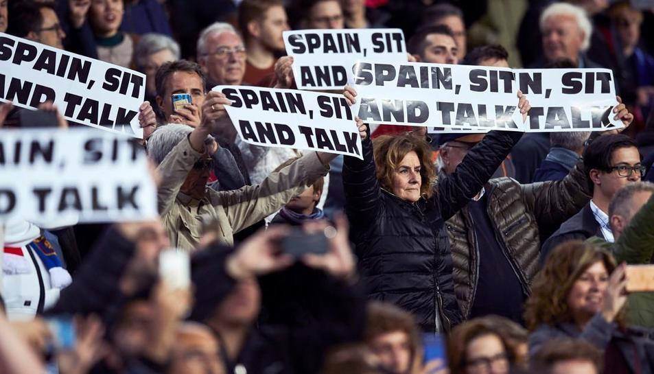 Espectadors del Camp Nou mostren rètols de «Spain, Sit and Talk» durant el partit de Champions contra l'Slavia de Praga.