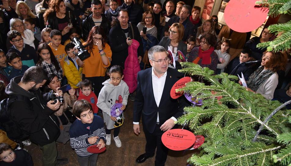 L'alcalde ha ajudat els infants a col·locar els seus desitjos a l'arbre.
