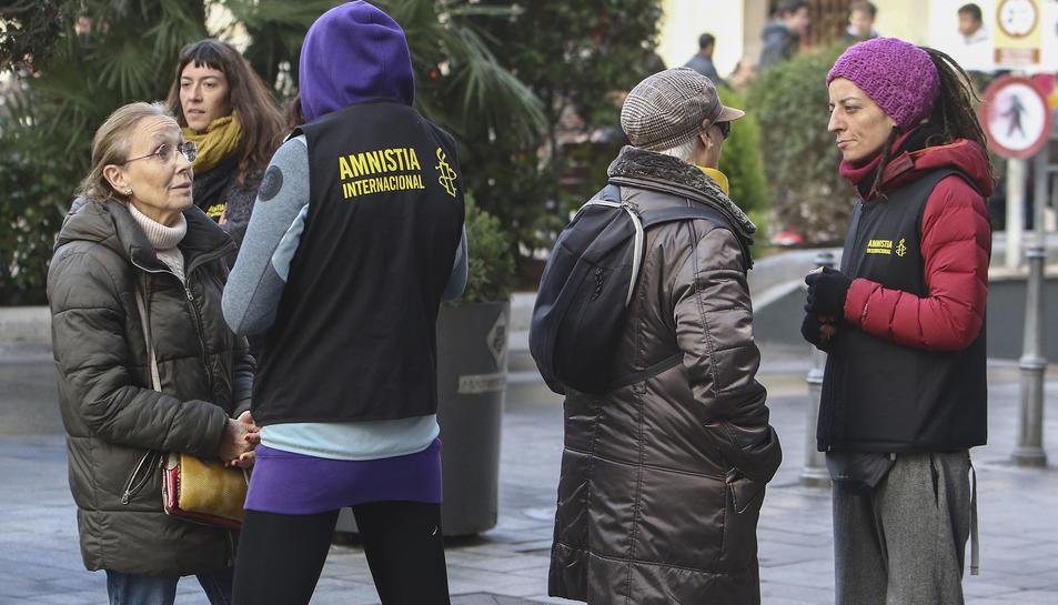 Voluntaris d'Amnistia Internacional dialoguen amb alguns vianants a la plaça Prim.