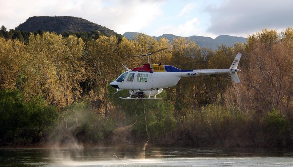 Pla general d'un helicòpter buidant la càrrega d'insecticida biològic BTI al riu Ebre, a l'alçada de l'assut de Xerta (Baix Ebre), contra la mosca negra.