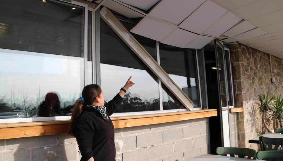 Una treballadora mostra els danys que van ocasionar en un bar els efectes de l'explosió a IQOXE.