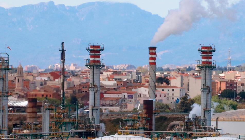 Xemeneies de la indústria química de Tarragona fumejant i, al fons, habitatges dels pobles del Morell i la Pobla de Mafumet.