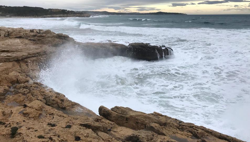 Pla general de les onades impactant contra les roques, a prop de la platja de l'Arrabassada.