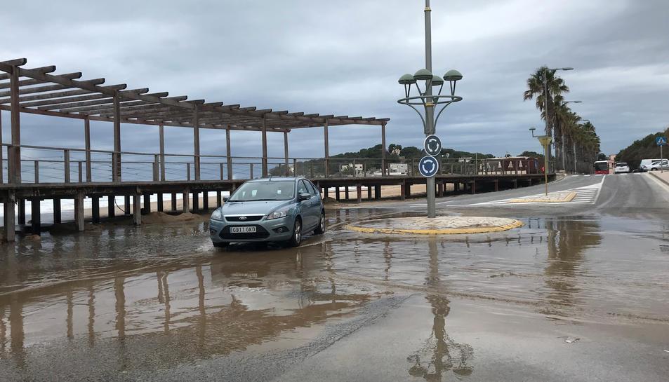 Un cotxe intentant passar per una rotonda amb tolls d'aigua de mar, a la platja de l'Arrabassada de Tarragona, a causa del temporal.