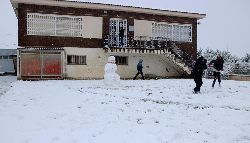 Uns nois fent una guerra de boles de neu durant el temporal, a Gandesa.