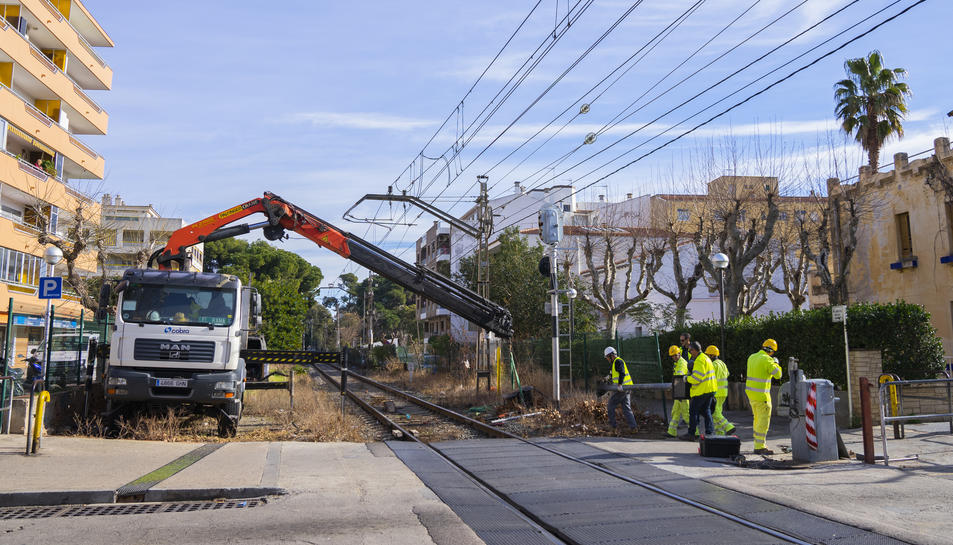 Operaris d'Adif retirant el pas a nivell del carrer de Barcelona de Salou el passat 13 de gener.