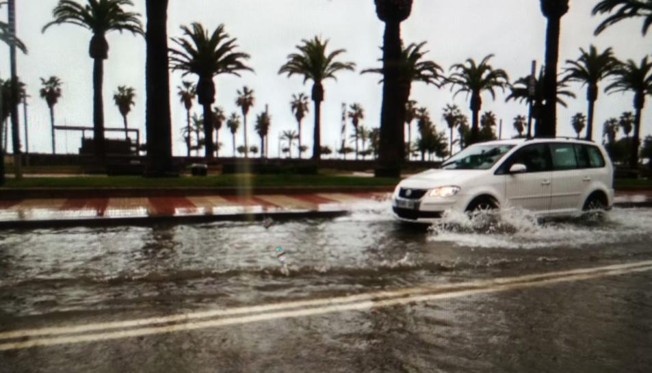 Un cotxe circulant pel passeig inundat.