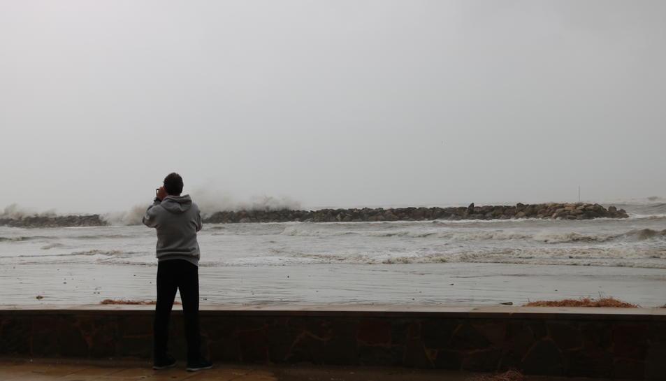 Un home d'esquenes fent una foto a les fortes onades que s'han registrat avui a les platges de Cunit.