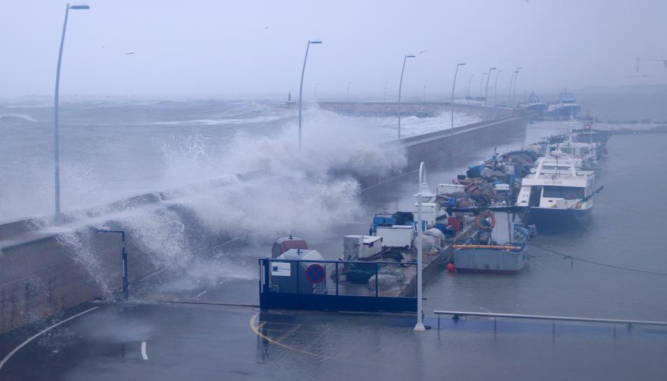 Pla general de les onades sobrepassant el moll pesquer del port de l'Ampolla.