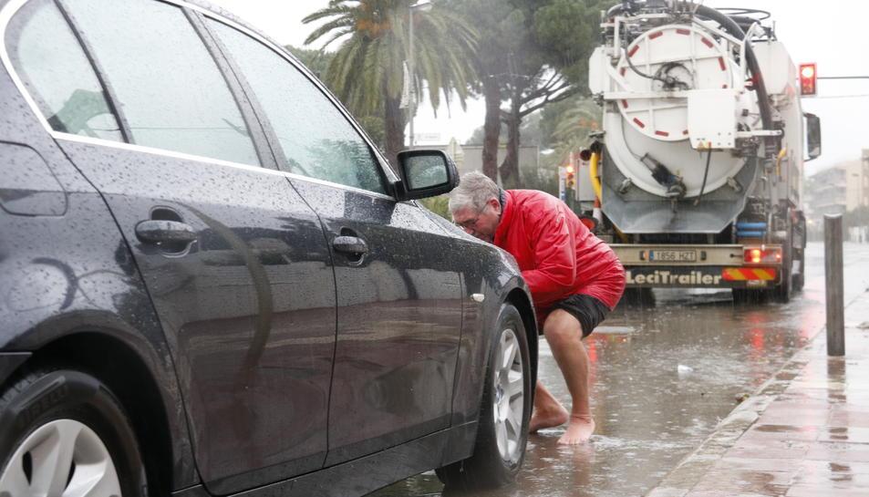 Un turista francès, descalç, amb el vehicle avariat, a l'avinguda de la Diputació de Cambrils, tallada per inundació.