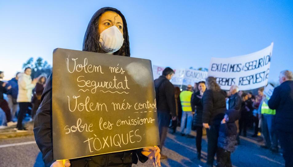 Una manifestant mostra una pancarta exigint més seguretat, en la concentració a l'N-340.