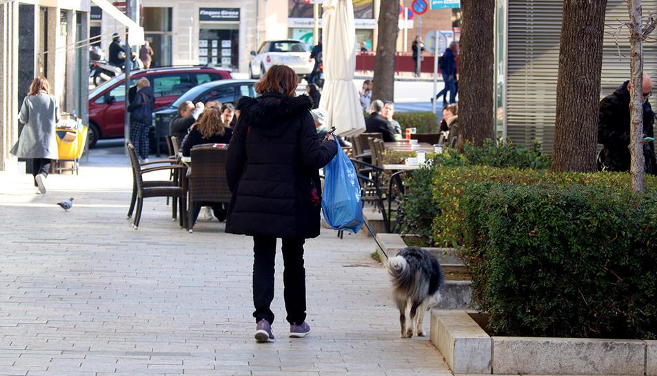 Una dona passejant un gos pel centre de Girona