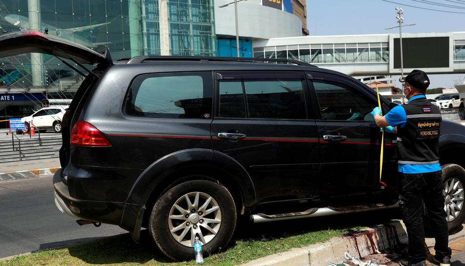 Un policia tailandès inspecciona el vehicle d'una de les víctimes del tiroteig
