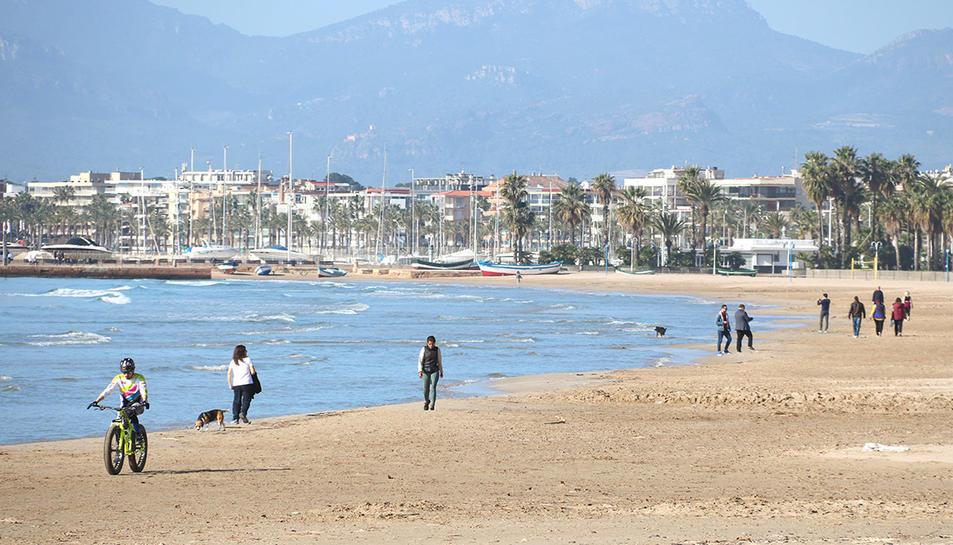 La platja de Salou i de persones passejant-hi, en ple hivern.