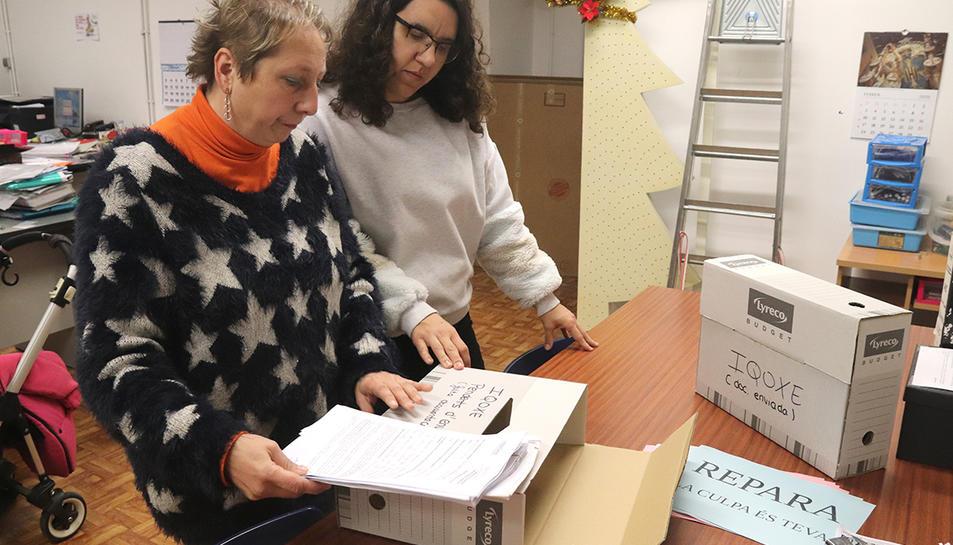 La presidenta de l'Associació de Veïns de Bonavista, Loli Gutiérrez, repassant carpetes amb documentació sobre l'explosió a IQOXE, amb una altra membre de l'entitat.