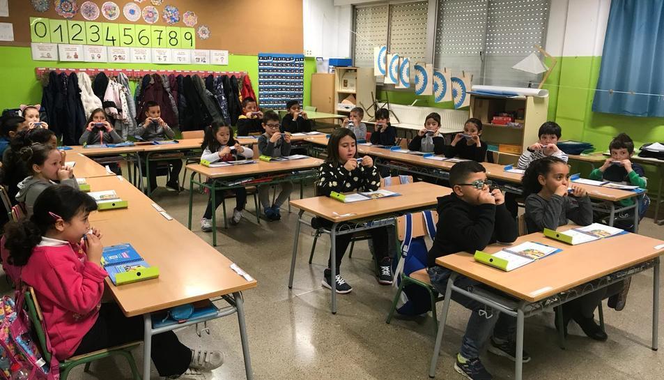 Alumnes de primer de primària de l'escola Mossèn Ramon Bergadà tocant l'harmònica.