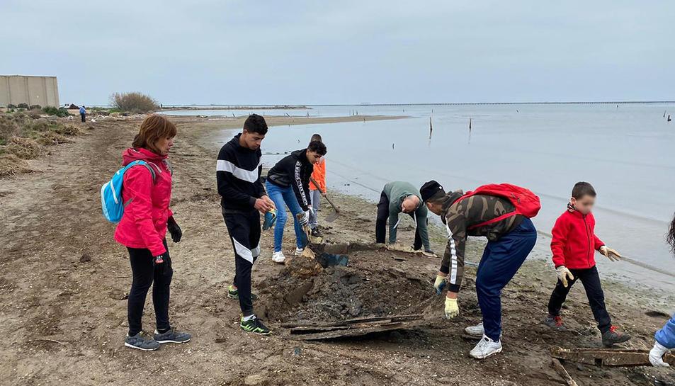 Voluntaris recollint brossa després de la llevantada a la costa de la badia dels Alfacs.