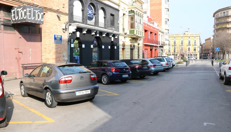 Pla general del carrer on van passar els fets amb els bars al costat i alguns cotxes aparcats.