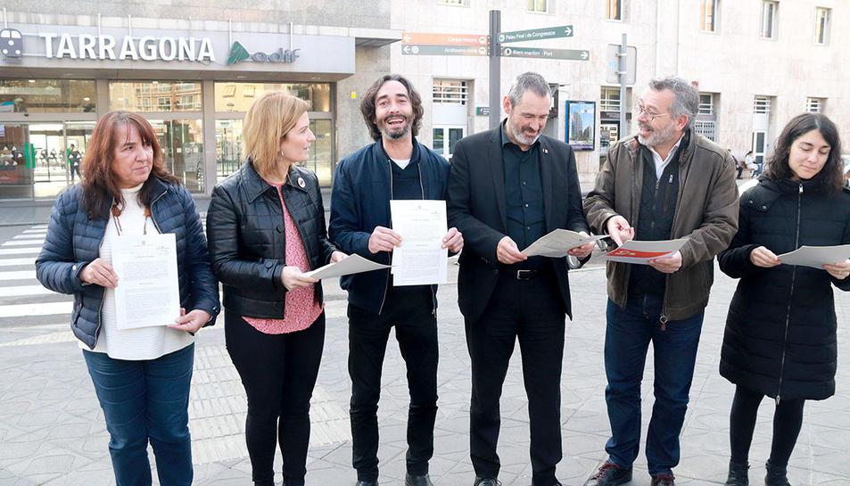 Els representants polítics del Camp de Tarragona amb la proposta de resolució que presentaran al Parlament, evidenciant la unitat davant l'estació de tren de Tarragona.