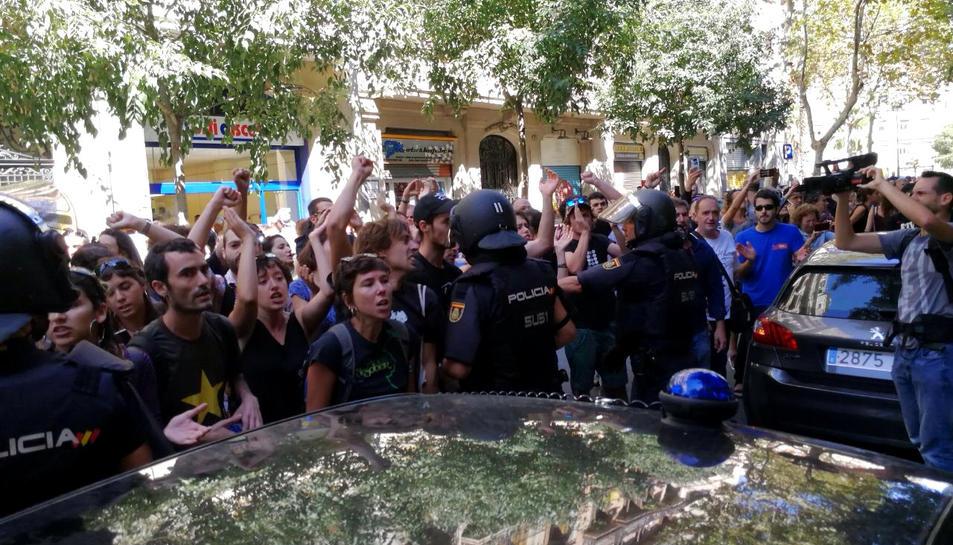 La policia espanyola envoltant la seu de la CUP, mentre simpatitzants criden en contra de l'actuació i en favor de l'1-O, el 20 de setembre de 2017.