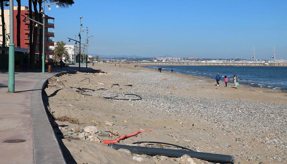El passeig i la platja de la Pineda, a Vila-seca, plena de pedres i restes de tubs.