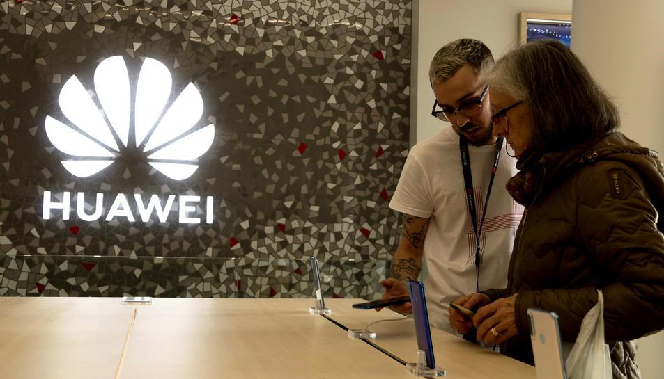 Un dependent mostra a una senyora un dispositiu mòbil a la botiga de Huawei de plaça Catalunya
