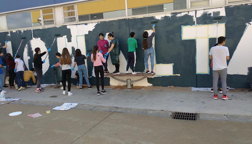 Un grup d'alumnes pintant el mur