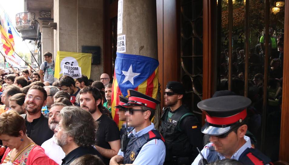 Diputats de diverses formacions davant de la seu d'Economia, davant de Mossos i Guàrdia Civil entre estelades i diverses pancartes a les parets de l'edifici, el 20 de setembre de 2017